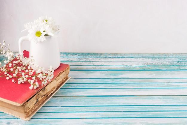 Gänseblümchenblumen im weißen krug auf buch