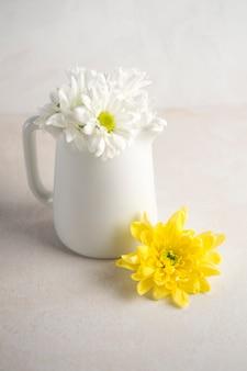 Gänseblümchenblumen im weißen krug auf tabelle