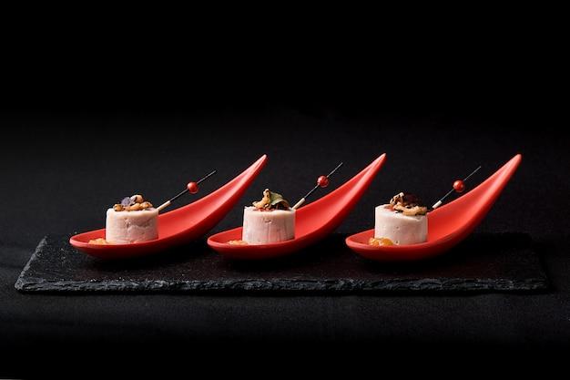 Gänseleberpastete, foie gras, serviert auf schwarzem stein in japanischen roten löffeln. paste serviert mit marmelade und nüssen. fusion food-konzept, zurückhaltend, kopierraum.