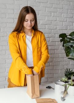 Gärtner, der ein geschenk mit einer pflanze vorbereitet