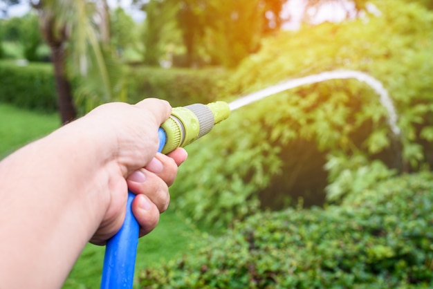 Gärtner, der schlauch der form des blauen wassers im garten wässert
