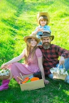 Gärtner glückliche familie auf frühlingspicknick im garten oder park. elternschaft zusammen freizeitkonzept.