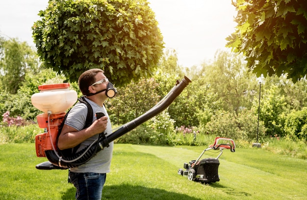 Gärtner in schutzmaske und brille sprüht giftige pestizidbäume