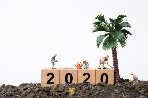 Gärtner kümmern sich um einen baum auf holzklotz nr. 2020