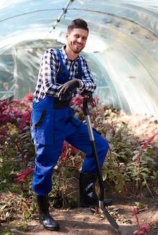Gärtner lehnt sich an eine schaufel