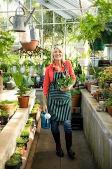 Gärtner mit topfpflanze und gießkanne im gewächshaus