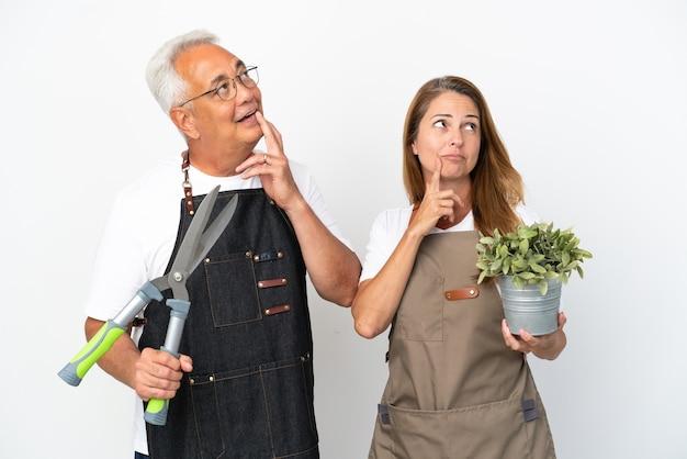 Gärtner mittleren alters, die eine pflanze und eine schere halten, die auf weißem hintergrund isoliert sind, denken beim nachschlagen eine idee