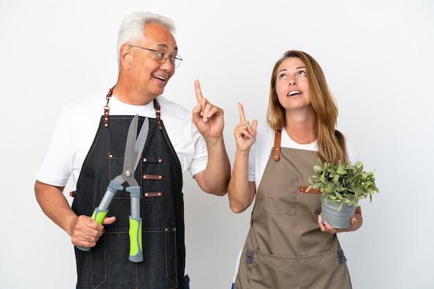 Gärtner mittleren alters, die eine pflanze und eine schere halten, die auf weißem hintergrund isoliert sind und beabsichtigen, die lösung zu realisieren, während sie einen finger hochheben