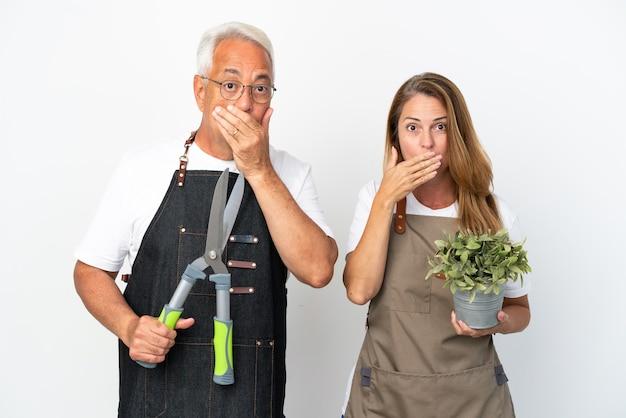 Gärtner mittleren alters, die eine pflanze und eine schere halten, die auf weißem hintergrund isoliert sind und den mund mit den händen bedecken, um etwas unangemessenes zu sagen