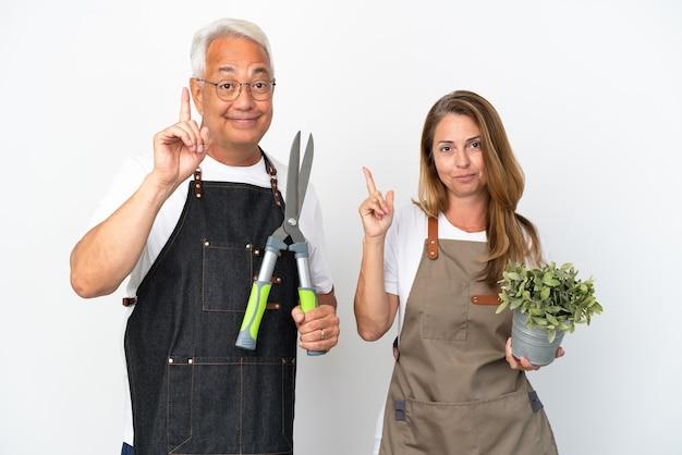 Gärtner mittleren alters, die eine pflanze und eine schere halten, die auf weißem hintergrund isoliert sind, zeigen und heben einen finger im zeichen des besten