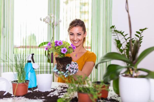 Gärtner pflanzt blumen in topf. junge frau, die blumen für das pflanzen während der gartenarbeit vorbereitet. menschen, gartenarbeit, blumenpflanzung und berufskonzept