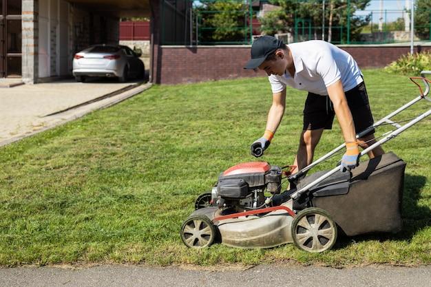 Gärtner schraubt den benzindeckel des rasenmähers ab, um den kraftstofftank zu füllen