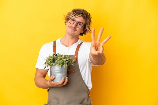 Gärtnerblonder mann, der eine pflanze lokalisiert hält