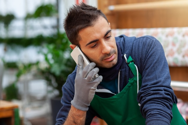 Gärtnerflorist, der am telefon in einem blumenladen mit anlagen spricht.