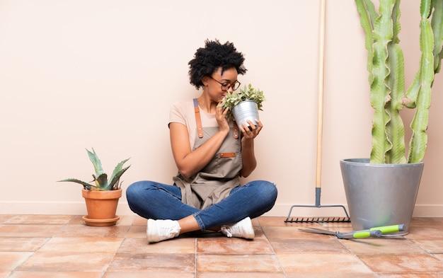 Gärtnerfrau, die auf dem boden sitzt
