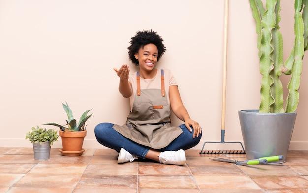 Gärtnerfrau, die auf dem boden um anlagen sitzt