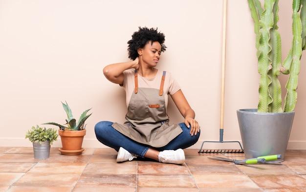 Gärtnerfrau, die auf dem boden unter anlagen sitzt