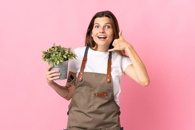 Gärtnerfrau, die eine pflanze lokalisiert auf rosa wand hält, die telefongeste macht. rufen sie mich zurück zeichen
