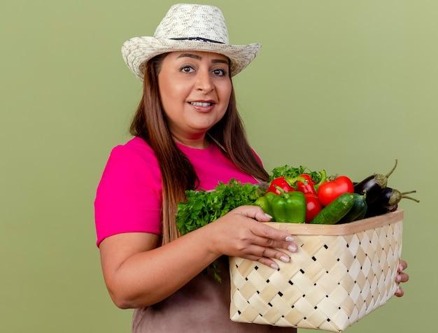 Gärtnerfrau mittleren alters in der schürze und im hut, die kiste voll des gemüses hält, das kamera mit lächeln auf gesicht steht, das über hellem hintergrund steht