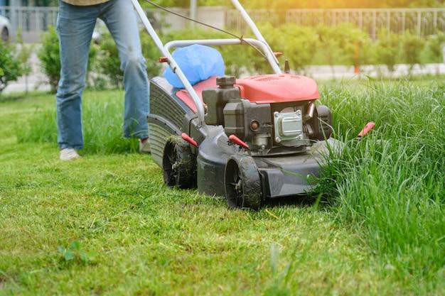 Gärtnerfrauenbeine, die gras mit rasenmäher mähen