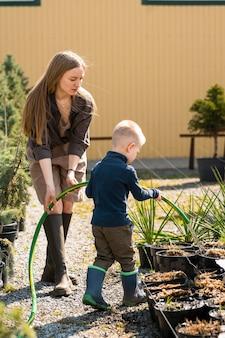 Gärtnerin bringt ihrem sohn bei, die pflanzen mit einem schlauch zu gießen
