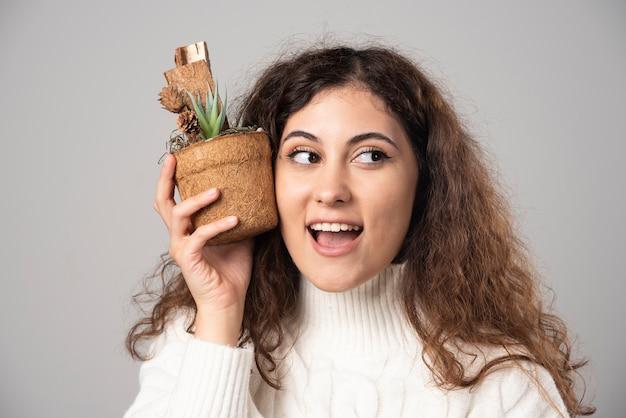 Gärtnerin der jungen frau, die eine pflanze auf einer grauen wand hält. hochwertiges foto