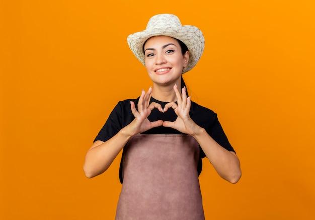 Gärtnerin der jungen schönen frau in der schürze und im hut, die front betrachten, die herzgeste mit den lächelnden fingern macht, die über orange wand stehen