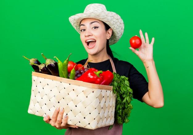Gärtnerin der jungen schönen frau in der schürze und im hut, die korb voll des gemüses halten, das das glückliche und aufgeregte stehen der tomate über grüner wand zeigt
