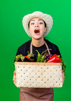Gärtnerin der jungen schönen frau in der schürze und im hut, die korb voller gemüse halten, die mit glücklichem gesicht schreien über grüner wand schreien