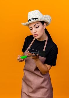 Gärtnerin der jungen schönen frau in der schürze und im hut, die mattock hält, die es mit interesse betrachtet, das über orange wand steht