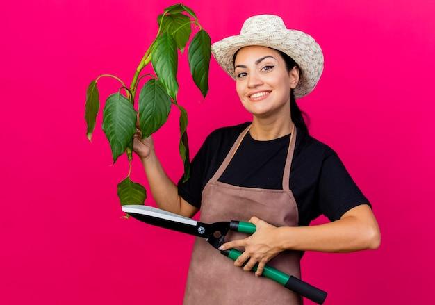Gärtnerin der jungen schönen frau in der schürze und im hut, die pflanze und heckenschere hält, die vorne lächelnd fröhlich über rosa wand stehend schaut