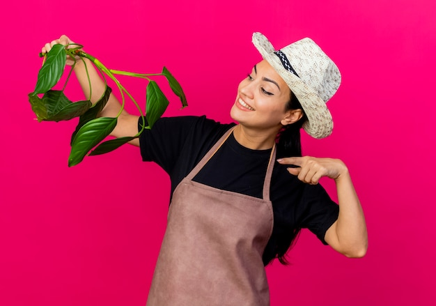 Gärtnerin der jungen schönen frau in der schürze und im hut, die pflanzenpunkt mit zeigefinger an ihm lächelnd über rosa wand stehend halten