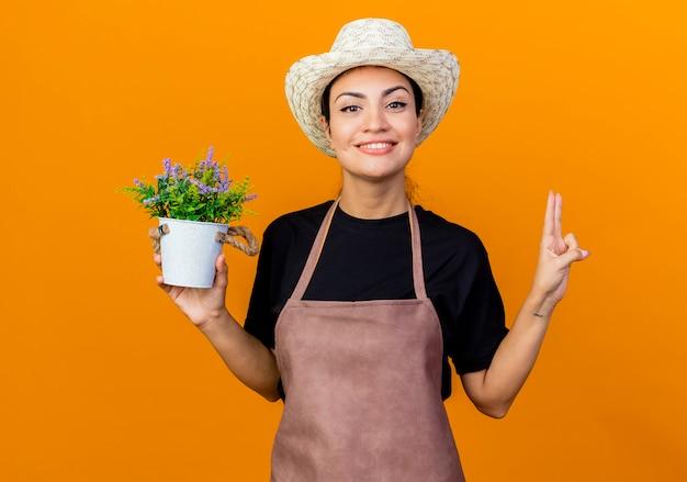 Gärtnerin der jungen schönen frau in der schürze und im hut, die topfpflanze hält, die vorne lächelnd zuversichtlich zeigt, nummer zwei stehend über orange wand