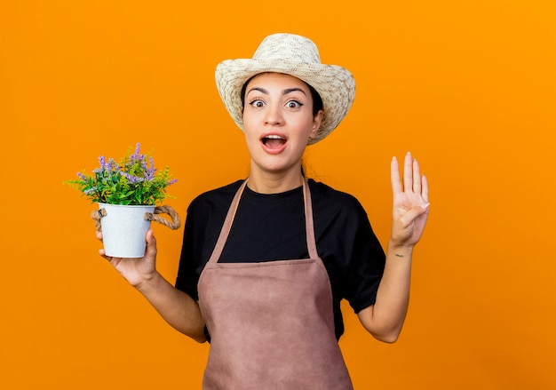 Gärtnerin der jungen schönen frau in der schürze und im hut, die topfpflanze hält, die vorne überrascht zeigt, zeigt nummer vier, die über orange wand steht