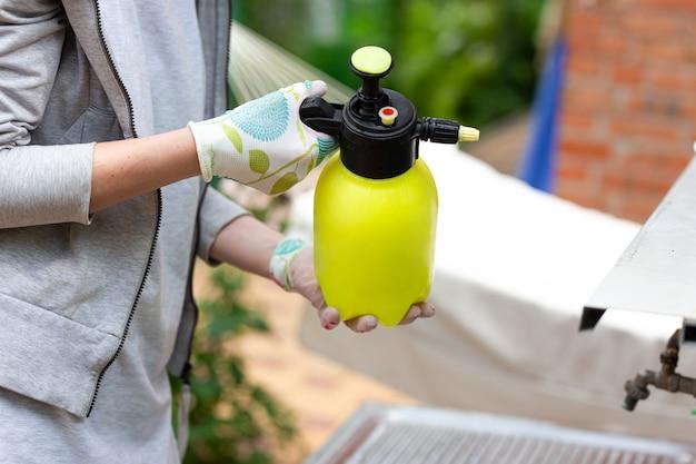 Gärtnerin, die einen sprüher mit pestiziden hält.