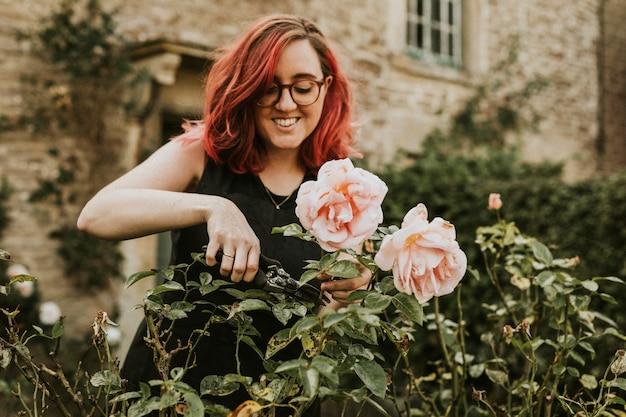 Gärtnerin, die rosa rose mit gartenschere schneidet