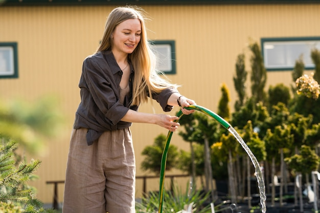 Gärtnerin gießt die pflanzen im gewächshaus