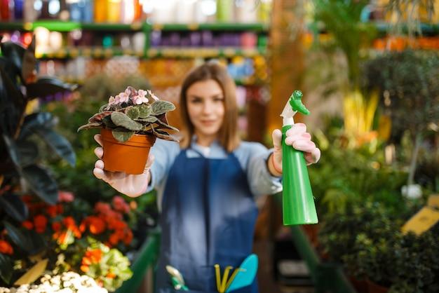 Gärtnerin mit blumen- und gartensprayladen für die gartenarbeit. frau verkauft pflanzen im blumengeschäft, verkäufer
