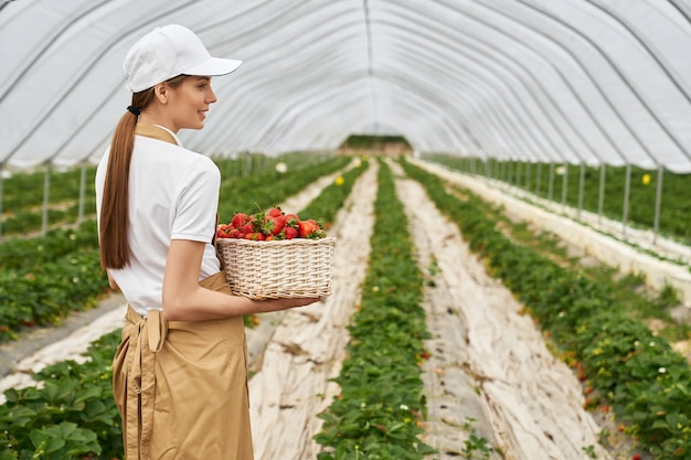 Gärtnerin mit korb mit frischen erdbeeren