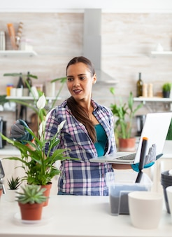 Gärtnerin mit laptop zu hause beim dekorieren der küche mit blumen