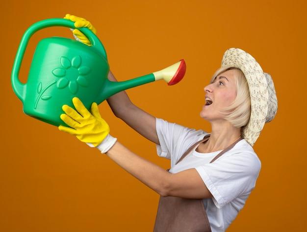 Gärtnerin mittleren alters in gärtneruniform mit hut und gartenhandschuhen, die in der profilansicht steht und eine gießkanne hält und versucht, wasser daraus zu trinken
