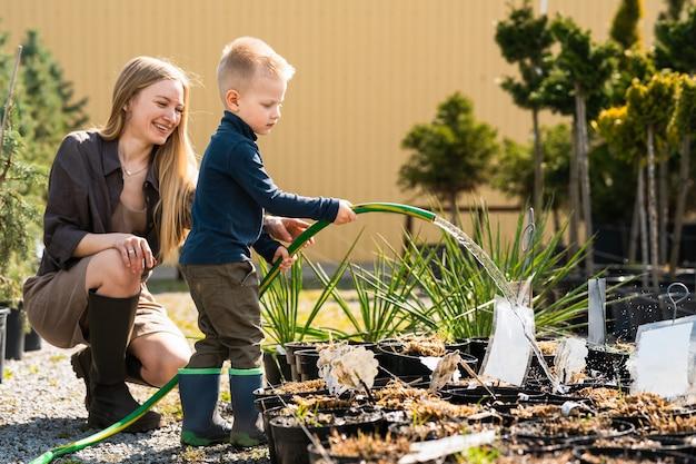 Gärtnerin und ihr sohn gießen die pflanzen in töpfen mit einem schlauch