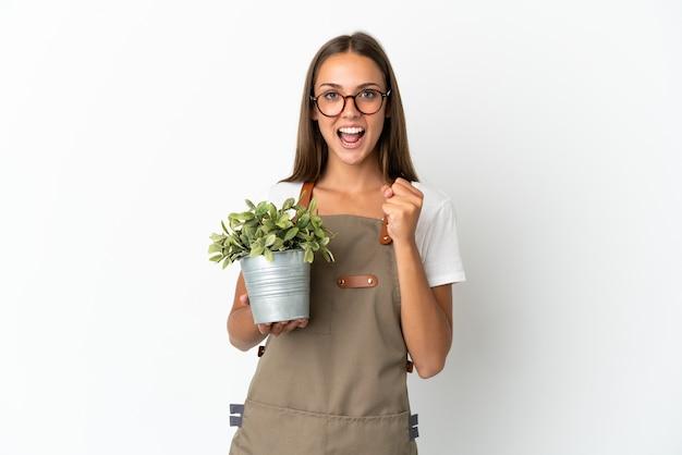 Gärtnermädchen, das eine pflanze über isoliertem weißem hintergrund hält, der einen sieg in der siegerposition feiert