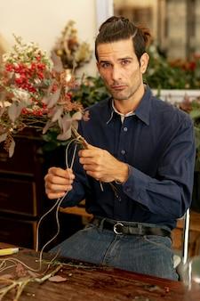 Gärtnermann mit langen haaren, die ein seil schneiden