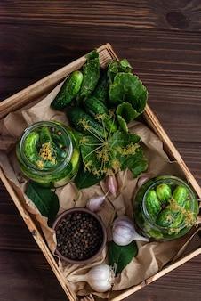 Gärung von gurken in gläsern. rohe gurken, dillblumen, kirschblatt, meerrettichblatt, gewürze und kräuter auf einem tablett, konzept der biologischen und gesunden ernährung, gurken einlegen.