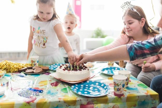 Gäste, die kerzen vom kuchen herausnehmen