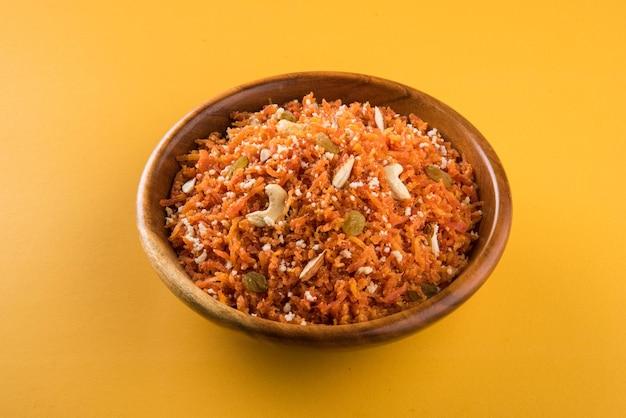 Gajar halwa ist ein süßer dessertpudding auf karottenbasis aus indien. mit cashewkernen, mandeln garniert und in einer schüssel auf buntem holzhintergrund serviert