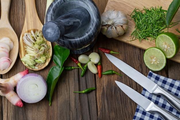 Galanga, zitronengras, kaffir-limettenblatt, schalotte, chilli, zitrone, knoblauch auf holzboden.