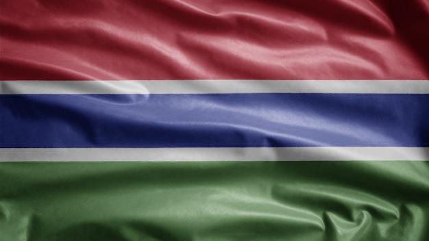 Gambische flagge weht im wind. nahaufnahme von gambia banner weht, weiche und glatte seide. stoff textur fähnrich hintergrund. verwenden sie es für das konzept für nationalfeiertage und länderanlässe.