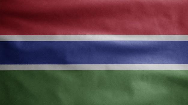 Gambische flagge weht im wind. nahaufnahme von gambia banner weht, weiche und glatte seide. stoff textur fähnrich hintergrund.